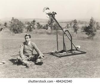 Mechanical golfer about to hit golf ball off man's head