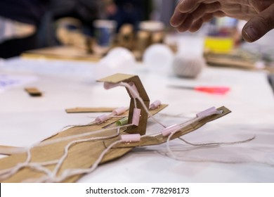 Mechanical hand of cardboard for children built during STEM activities in the classroom. Human hand and mechanical hand in contrast during educational activity for kids
