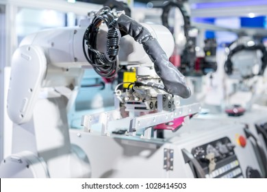 Mechanical hand robot loading automotive part working in manufacture factory