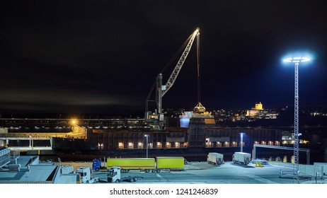 mechanical hydraulic clamshell grabbers loading coal on ship at night.
