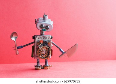 Mechanical kitchen chef robot knife spoon. Funny toy cooking character for restaurant food menu advertising poster. Friendly cyborg made electric wire lamp bulb transistor accessories. Pink backdrop.