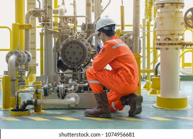 Mechanical specialist check oil pump centrifugal type and use walkie talkie talk to central control room to function test pump. Offshore oil and gas industry maintenance activities.