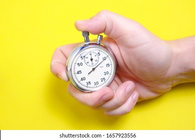 Mechanical stopwatch in a man's hand on a yellow background