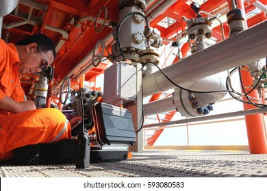 Mechanical technician hooked up to junction box of flow meter for check and inspect, performing various mechatronic checks, outputting the condition in a graph.