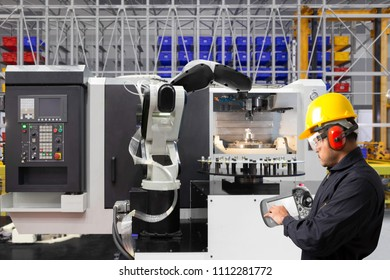 Mechanical technician operating programming on control panel of robotic arm of the cnc milling machine in manufacture. automate processes production on factory, technology of industry concept.