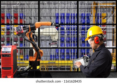 Mechanical technician operating programming on control panel of robotic arm in production line of high technology manufacturer factory site