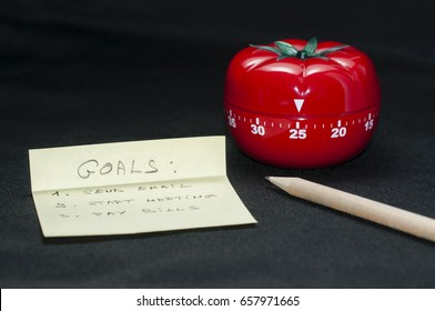 Mechanical Tomato shaped kitchen timer for cooking, studying and working with pencil and goal list.