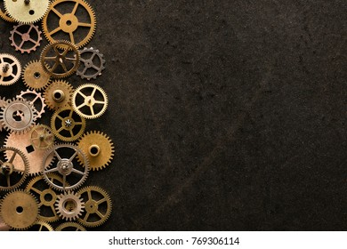 mechanical watch repairing concept. cogwheels on the left of metal desk.