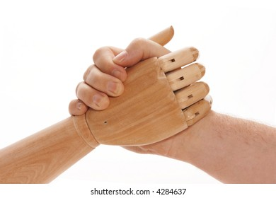 Mechanical wooden hand arm wrestling with man's hand.