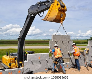 Mechanically Stabilized Earth (MSE) wall construction with an excavator lifting a concrete wall panel while two workers guide the panel into place and onto nylon pins to ensure proper installation.