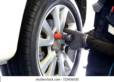 Mechanician changing car tire and whell in auto repair service center, Automotive mechanic tightening using a torque wrench, as background automotive concept.