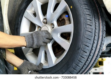 Mechanician changing car tire and whell in auto repair service center, Automotive mechanic tightening using a screw with hands, as background.