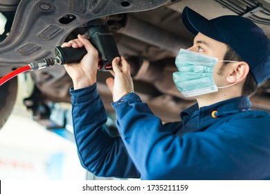 Mechanician changing car wheel in auto repair shop wearing a mask, coronavirus concept - Shutterstock ID 1735211159