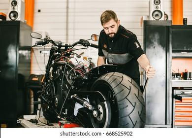 Mechanician changing motorcycle wheel in bike repair shop. Professional motorcycle mechanic working in bike repair service.