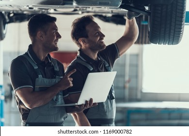 Mechanics Checking Wheel Bearings in Car Workshop. Two Caucasian Adult Technician Master in Uniform Repairing Car. Repairman Looking at Car Using Laptop. Auto Service Concept