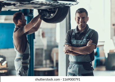 Mechanics Checking Wheel Bearings in Car Workshop. Two Caucasian Adult Technician Master in Uniform Repairing Car. Repairman Looking at Camera with Crossed Arms. Auto Service Concept