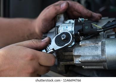 Mechanics with dirty hands repair broken starter on car/ Automotive service