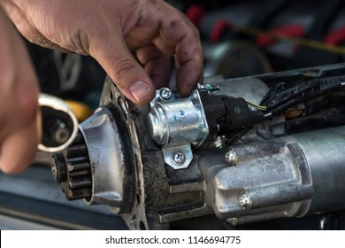 Mechanics with dirty hands repair broken starter on car/ Automotive service