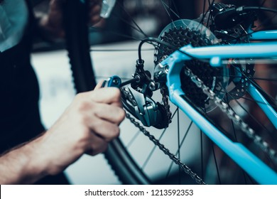 Mechanics Hand Repairing Bicycle in Bike Workshop. Closeup of Male Muscular Hand Examining and Fixing Modern Cycle Transmission System. Bike Maintenance and Sport Shop Concept