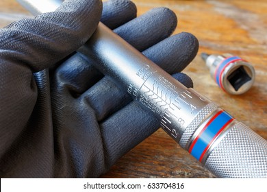 Mechanic's hand in the working glove holds the torque wrench