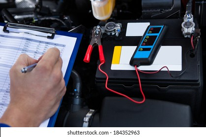 Mechanic's hand writing on clipboard with pliers connected to multimeter on car engine