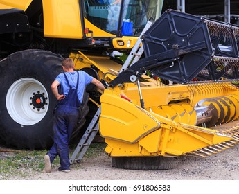 The mechanics repair the yellow Combine harvester in the farm yard. Concept theme repair, mechanics, production, industry, agribusiness, production of food, agricultural production. Not staged photo.