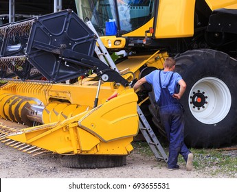 The mechanics repair the yellow combine harvester in the farm yard. Concept theme: repair, mechanics, production, industry, agribusiness, production of food, agricultural production.