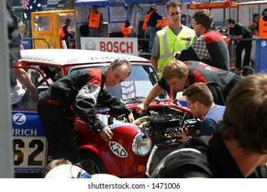Mechanics working on a car in the pits
