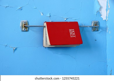 Mechanicville, NY/USA- December 8, 2018: A horizontal HIGH DEFINITION image of a red Bible in a dilapidated blue washroom in an abandoned Catholic school in upstate NY.