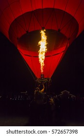 The mechanism of the hot air balloon requires compression of the heat from the gas.Close up  a burner heating the air inside of the balloon at night