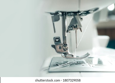 Mechanism of a sewing machine close up. White sewing machine needle with thread with copy space for text. The concept of the garment industry, technology. Photo for garment production. - Shutterstock ID 1807329058