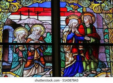 MECHELEN, BELGIUM - JANUARY 31, 2015: Stained Glass window depicting Mary of Clopas, Mary Magdalene, Mother Mary and Saint John the Apostle on Good Friday, in the Cathedral of Mechelen, Belgium.