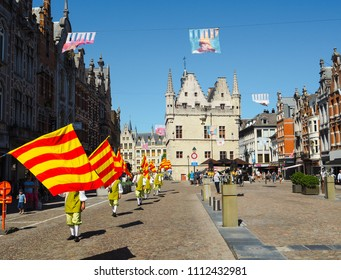 Mechelen, Belgium - May 2018: Men participating in the Hanswijk procession, carrying the city flag of Mechelen while walking on the Ijzerenleen