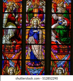 MECHELEN, BELGIUM - NOVEMBER 4, 2016: Stained Glass window depicting the Coronation of Mother Mary by the Holy Trinity, in the Cathedral of Saint Rumbold in Mechelen, Belgium.