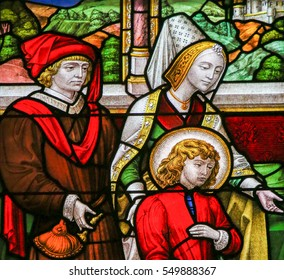 MECHELEN, BELGIUM - NOVEMBER 4, 2016: Stained Glass in Mechelen Cathedral, Belgium, depicting a noble family (16th Century)