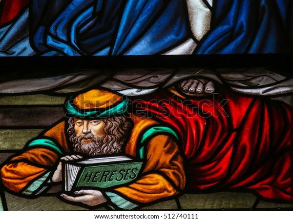 MECHELEN, BELGIUM - NOVEMBER 4, 2016: Stained Glass window depicting a heretic, in the Cathedral of Saint Rumbold in Mechelen, Belgium.
