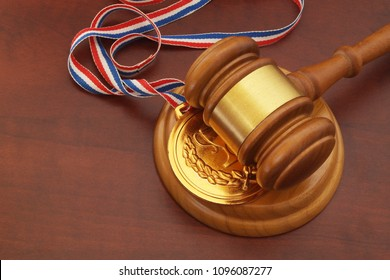 Medal and wooden judge's gavel, arbitration court concept.