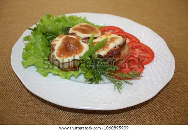 Medallions of pork on a leaf of lettuce.