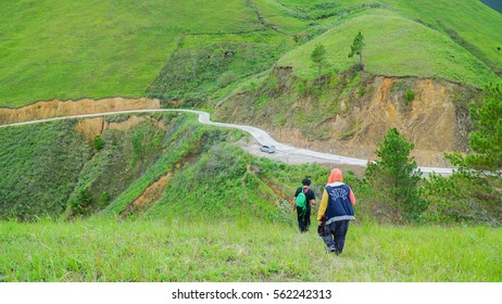 MEDAN, INDONESIA - DECEMBER 11, 2016: People hiking down of a grassy hill at Samosir Island, Indonesia, near the famous  Lake Toba, with the green landscape view