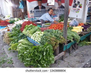 Medan, Indonesia - March 17, 2019 : A woman who sells vegetables and also supports Jokowi Amin.
