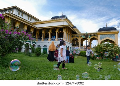 Medan, North Sumatera/Indonesia-November 2018: The kids are playing bubbles at the lawn of Istana Maimun (Maimun Palace). This palace,the heritage of Deli Sultanate, is a popular destination in Medan.