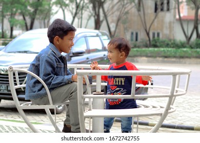 Medan, North Sumatra, Indonesia - March 2020: Children love to sit outside while telling stories and smiling