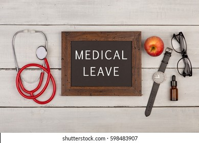 """Medecine concept - blackboard with text """"Medical leave"""", eyeglasses, watch and stethoscope on white wooden background"""