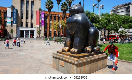 """Medellin, Antioquia / Colombia - November 10 2015: Activity in the Botero Plaza. Sculpture """"Gato"""" by Fernando Botero, a famous artist from Medellin. Botero Plaza is a place visited by many tourists"""