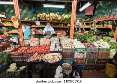 Medellin, Colombia / August 10. 2017: Man standing behind his market stand with a lot of vegetables.