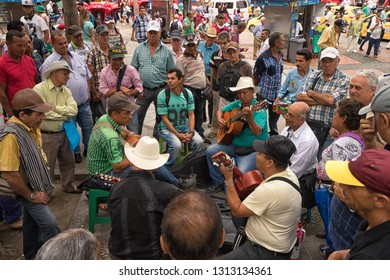 Medellin, Colombia - July 23, 2018: men playing guitars in a park surrounded by people