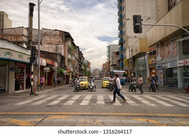 Medellin, Colombia - July 23, 2018: woman walking on crosswalk with vehicles and motorbikes stopped behind