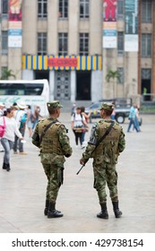 MEDELLIN, COLOMBIA - MARCH 14: Two military men standing on square with automatic weapon in hands and people around. El Circo Botero�´s latest exhibition sign in the background. Colombia 2015