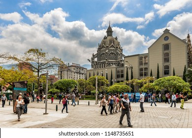 Medellin, Colombia - March 26, 2018: Tourists walking at Botero Plaza in Medellin, Colombia.   At the background is Palace of Culture Rafael Uribe and Coltejer Building, symbols of the city.