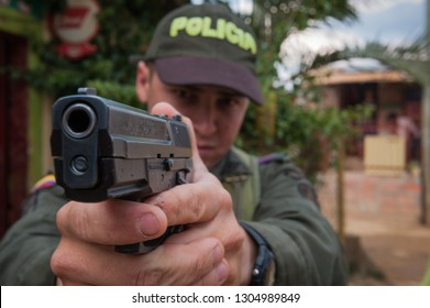 Medellin, Colombia,/South America- February 28, 2012: Colombian police officer demonstrates holding his firearm, a Sig Sauer SP2022, in a ready-to-fire stance.